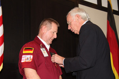 Ambassador Klaus Scharioth awards Tim Chopp the Order of Merit of the Federal Republic of Germany.